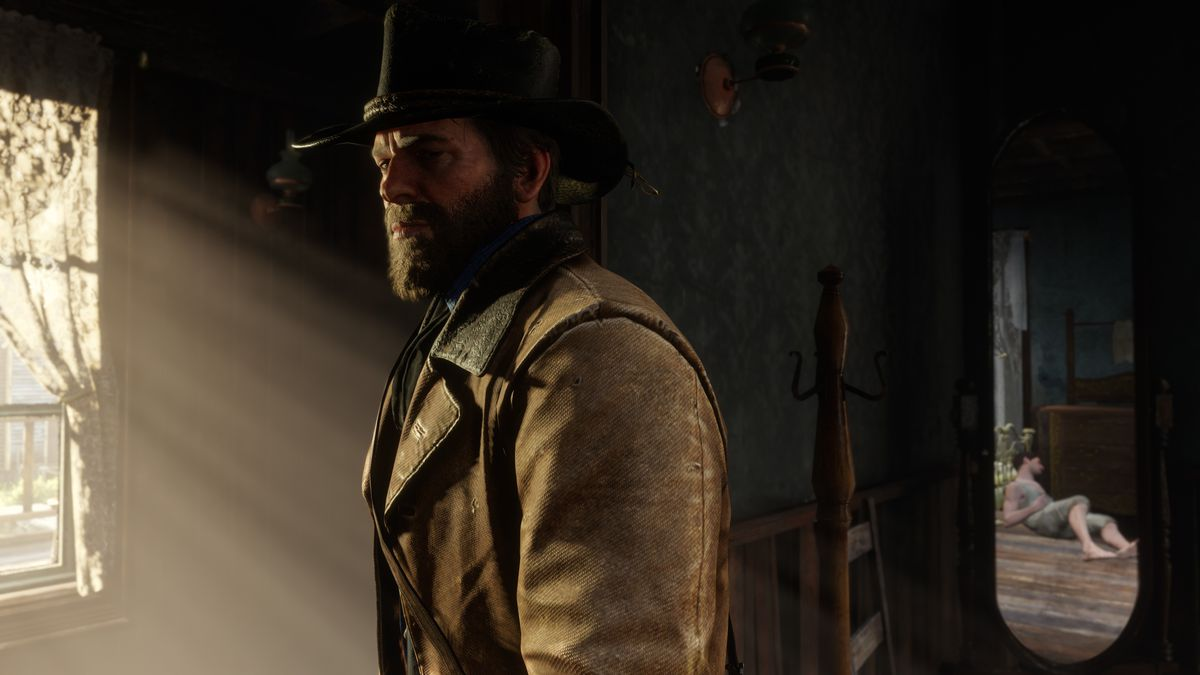a bearded man in a cowboy hat and tan overcoat, Arthur Morgan, stands inside a house with sunlight streaming in through a window in Red Dead Redemption 2