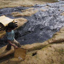 An Indian rag picker walks through contaminated water flowing out of an industrial unit in Jammu, India, Sunday, April 22, 2012. April 22 is observed as Earth Day every year as a tool to raise ecological awareness.