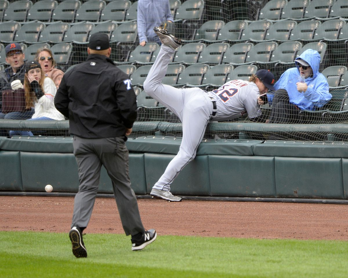 A baseball player falls into a net right next to a fan in a nearly empty section.