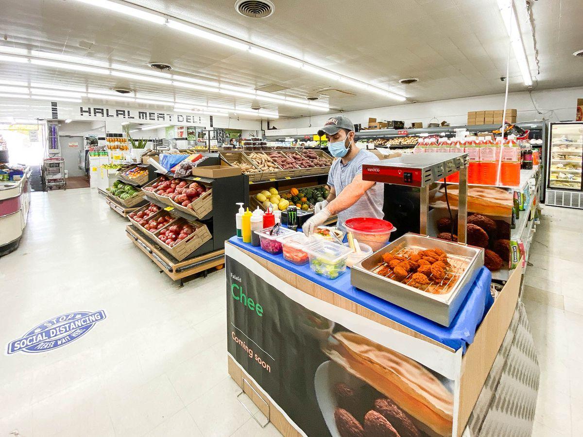 A man in a mask makes a falafel sandwich inside of a market.