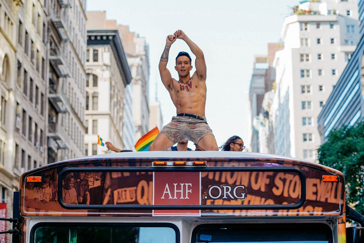 """Raif Derrazi rides a bus shirtless with the words """"Living With HIV""""at the World Pride march in New York City in June 2019."""
