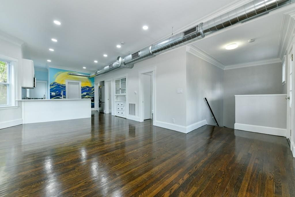 An expansive, empty room at the top of the stairs.