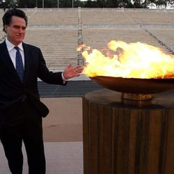 SLOC member Mitt Romney warms his hands near the Olympic flame in Athens, Greece, prior to a ceremony  Dec. 3, 2001.