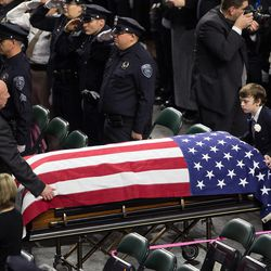 Jack Barney helps move the casket of his father, Unified police officer Doug Barney, into the Maverik Center in West Valley City on Monday, Jan. 25, 2016, prior to his funeral.