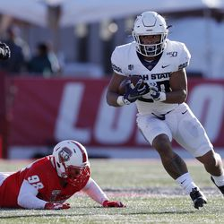 Utah State running back Jaylen Warren (20) carries past New Mexico defensive lineman Joey Noble (98) during the first half of an NCAA college football game on Saturday, Nov. 30, 2019 in Albuquerque, N.M. Warren was named to a 2020 Doak Walker Award watch list.