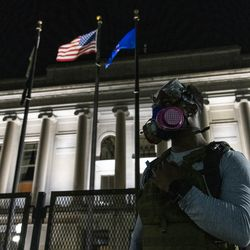 An activist stands in front of the Kenosha County Courthouse during a protest over the shooting of Jacob Blake, Tuesday, Aug. 25, 2020, in Kenosha, Wis.