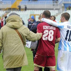 Livorno's Pasquale Schiattarella, center, and Pescara's Marco Verratti, right, confort each other as medics assists Livorno's Piermario Morosini, not shown, at the Pescara's Adriatico stadium, central Italy, Saturday, April 14, 2012, during a Serie B soccer match between Pescara and Livorno. Morosini, who was on loan from Udinese, fell to the ground in the 31st minute of the match and received urgent medical attention on the pitch. A defibrillator was also used on the 25-year-old. The match was called off, with the other players leaving the field in tears.