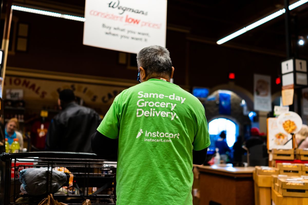 Wegmans grocery store interior with Instacart man worker and sign on shirt for same-day delivery