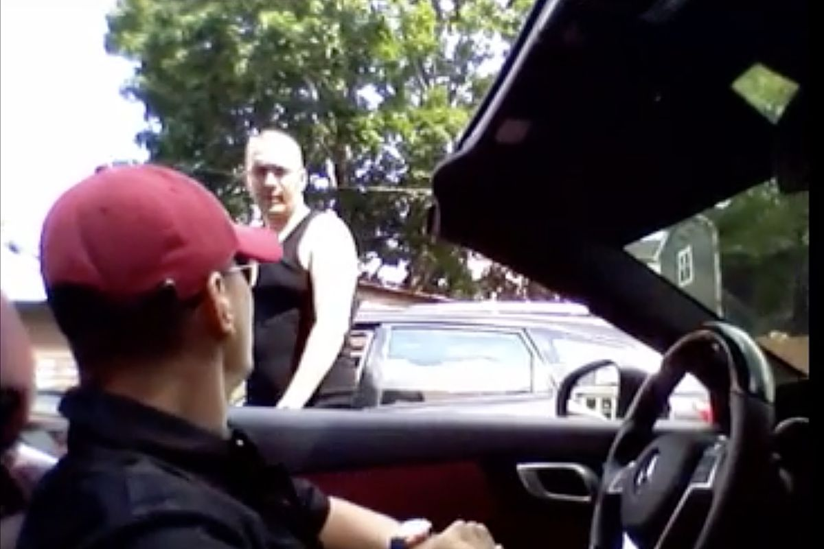 """Earl Casteel (standing) was seen in the viral cellphone video from which this image is taken being shot in both legs in 2015 in Irving Park by Thaddeus """"T.J."""" Jimenez (seated in the car)."""