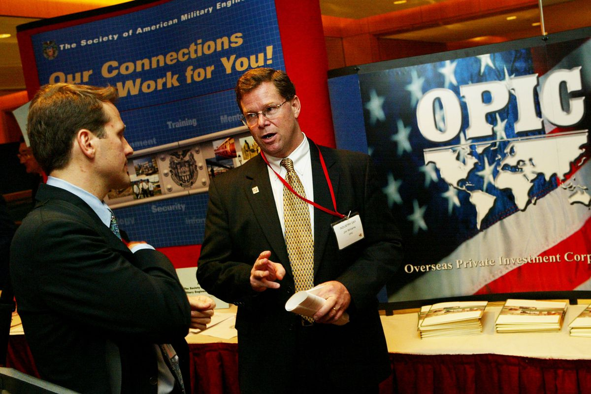 OPIC Regional Director of Insurance James Williams stands in front of a booth in an exhibit hall.