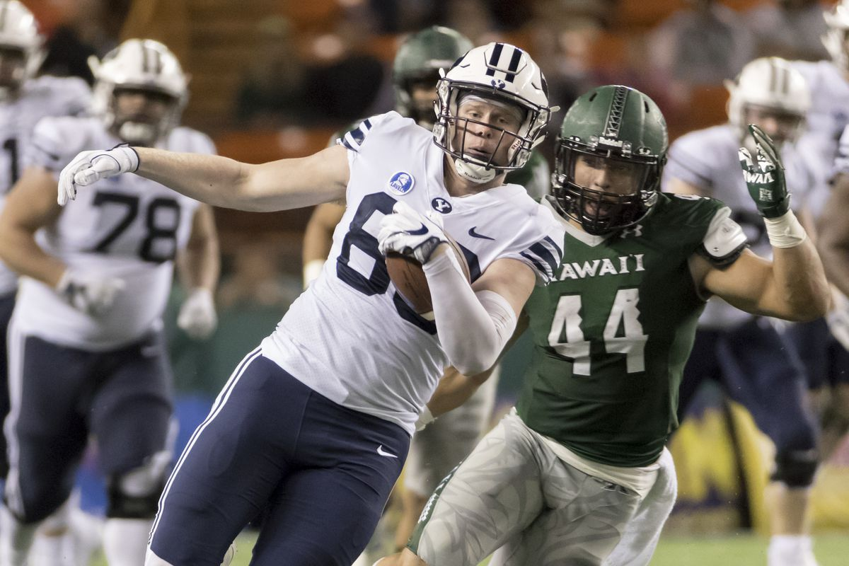 BYU tight end Matt Bushman left runs with the football while Hawaii linebacker Russell Williams Jr. (44) gives chase during the third quarter of an NCAA college football game, Saturday, Nov. 25, 2017, in Honolulu. (AP Photo/Eugene Tanner)