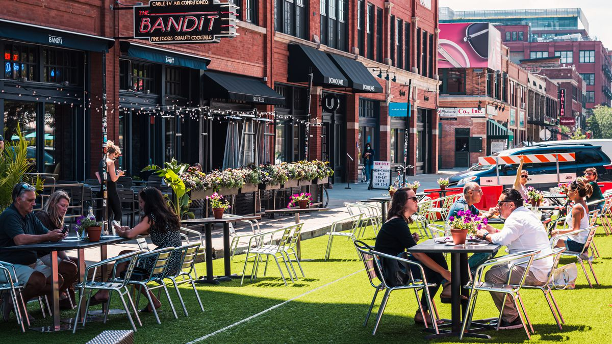 Folks sitting outside on patio furniture on artificial turfed streets.