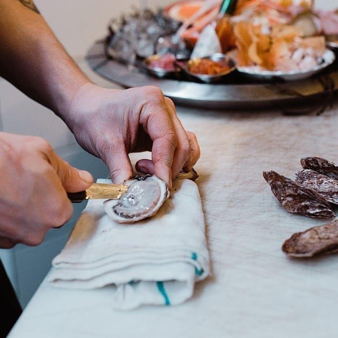 A hand shucking an oyster on a cutting board.