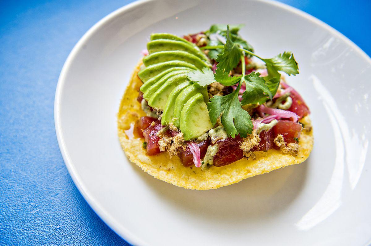 The surf and turf tostada comes with ahi tuna, dried pork machaca, charred jalapeno crema, pickled onion and avocado at Lola Coastal Mexican.