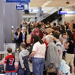 Holiday travelers gather around the baggage claim area at Salt Lake International Airport on Wednesday.