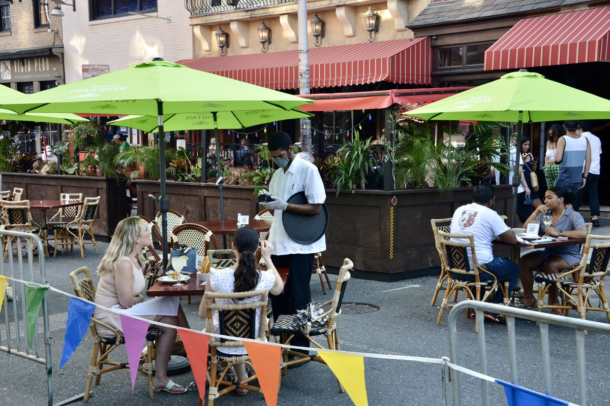 people dining at outdoor tables with green umbrellas, with metal fences with colorful flags and a server in a pandemic face mask