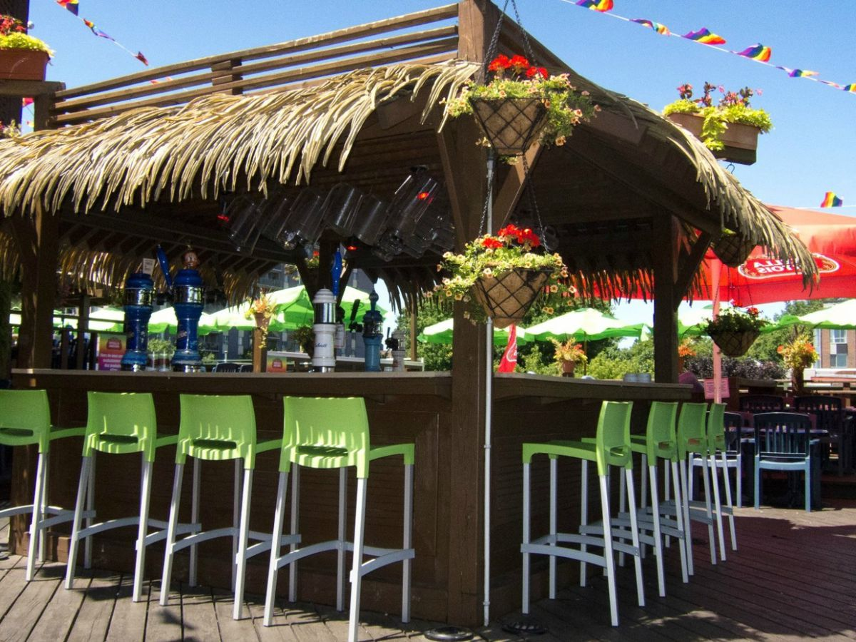 A cabana-like bar lined with palm fronds on a rooftop deck.
