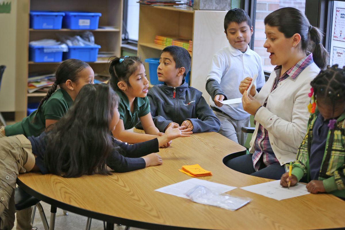 Instructional aid Maricela Berrospe, right, works with Kindergartners at Enlace Academy.  Much of the instruction at the school takes place in small groups.