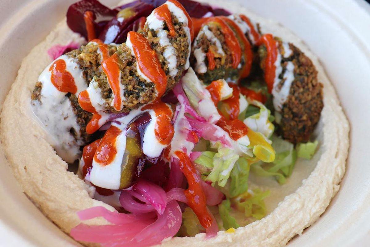 A bowl of hummus and falafel