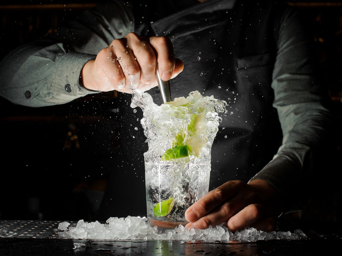 Bartender squeezing juice from fresh lime in a glass using a citrus press and splashing it out making an alcoholic cocktail