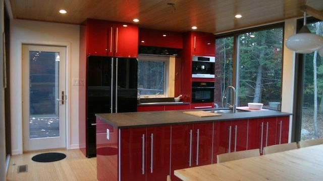 A kitchen area with red cabinets.
