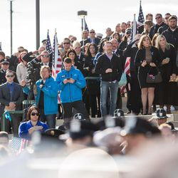 The crowd stands and watches as Unified police officer Doug Barney's casket is carried out of the Maverik Center following his funeral in West Valley City Monday, Jan. 25, 2016.