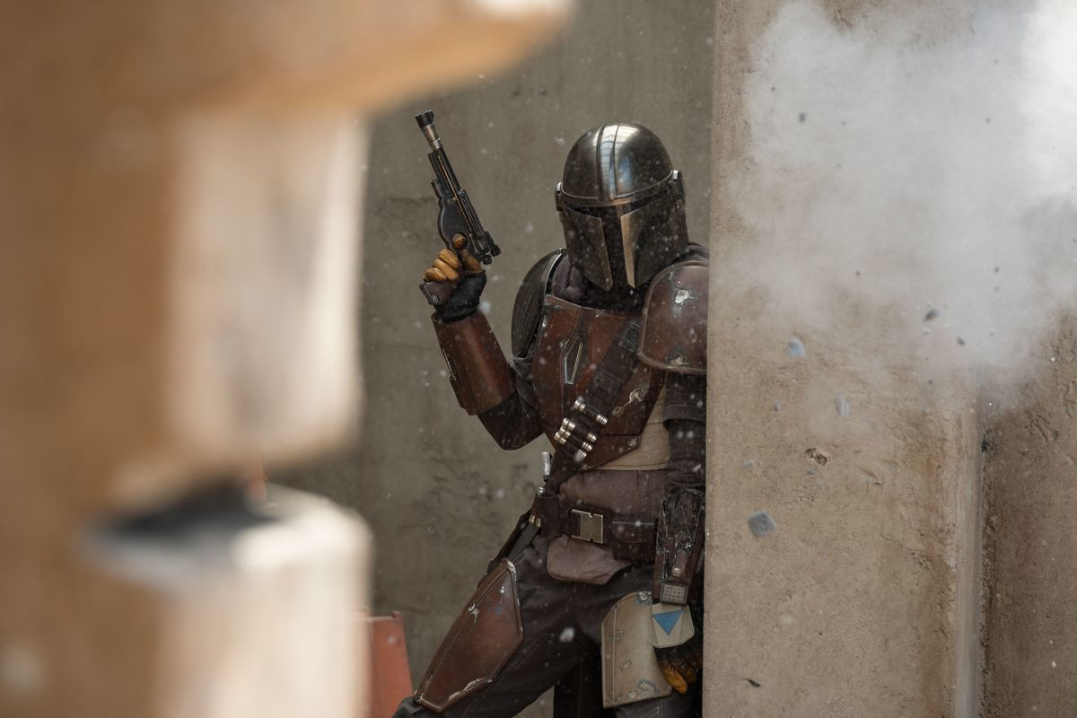 A man in armor holds up a weapon and dodges behind a wall.