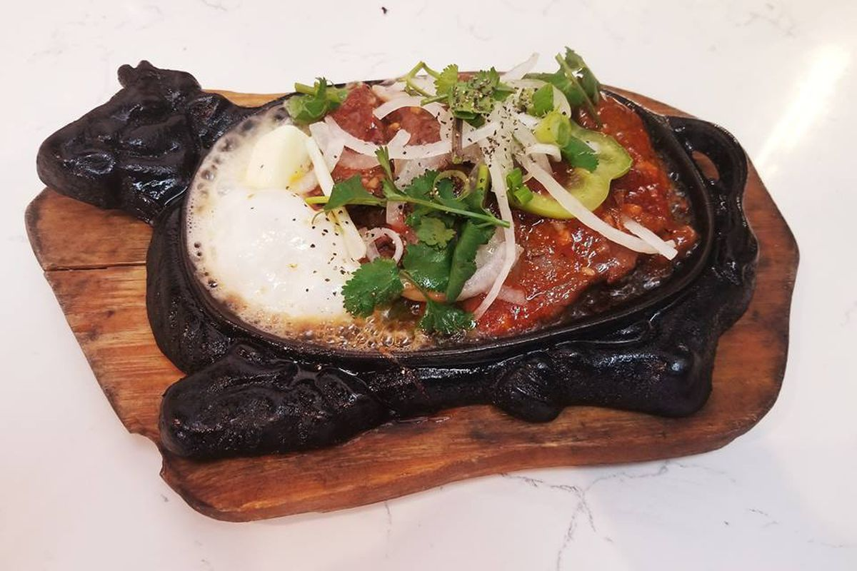 A Vietnamese beef and egg dish is served in a cow-shaped cast iron pan
