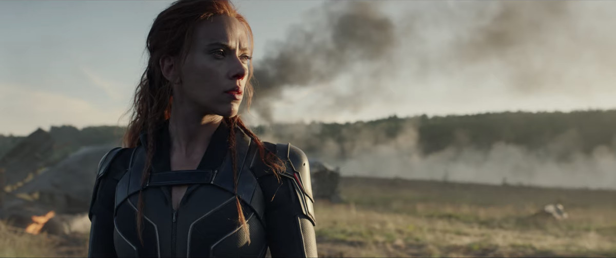 Scarlett Johansson as Natasha Romanoff/Black Widow looks cool posing in front of some smoke in a field, in a teaser trailer for Marvel Studios' Black Widow.