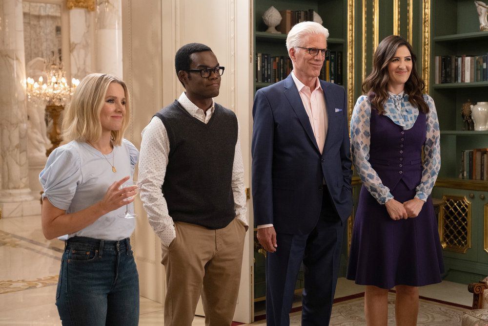 """Eleanor (Kristen Bell), Chidi (William Jackson Harper), Michael (Ted Danson), and Janet (D'Arcy Carden) smile in a screenshot from The Good Place season 4, episode 13, """"Whenever You're Ready"""""""
