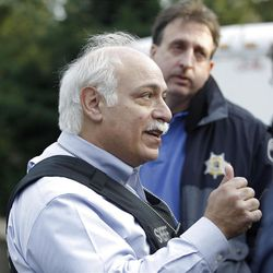 Pierce County Sheriff Paul Pastor speaks to the news media with detective Ed Troyer behind him, in front of the smoldering remains of a house near Fredrickson, Wash., Sunday, Feb. 5, 2012, where, according to a sheriff's spokesman, three bodies were were found. The bodies are believed to be Josh Powell and his two sons. The explosion occurred moments after a Child Protective Services worker brought the two boys to the home for a supervised visit. (AP Photo/John Froschauer)