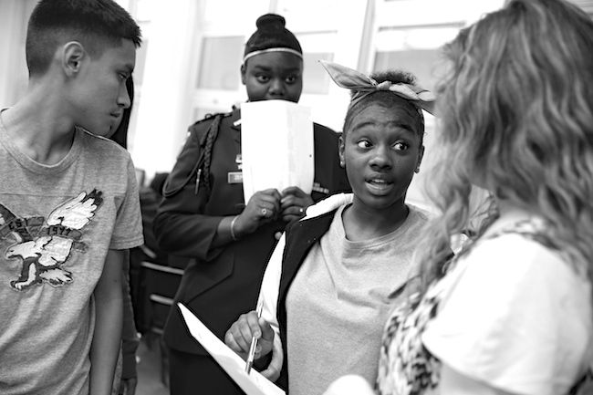 Manual students, left, check their work with English teacher Olivia Jones, right. Jones, like several teachers at Manual, are just starting out.