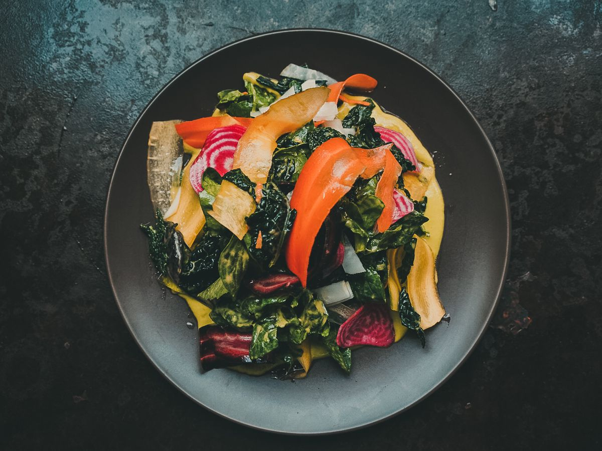 A salad with greens, orange peppers