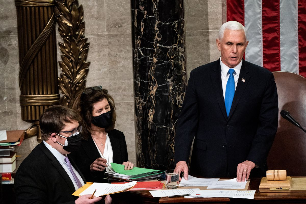 Pence, in a dark suit, white shirt, and bright blue tie, stands at the House speaker's podium, in front of a giant US flag. Aides hand him papers.