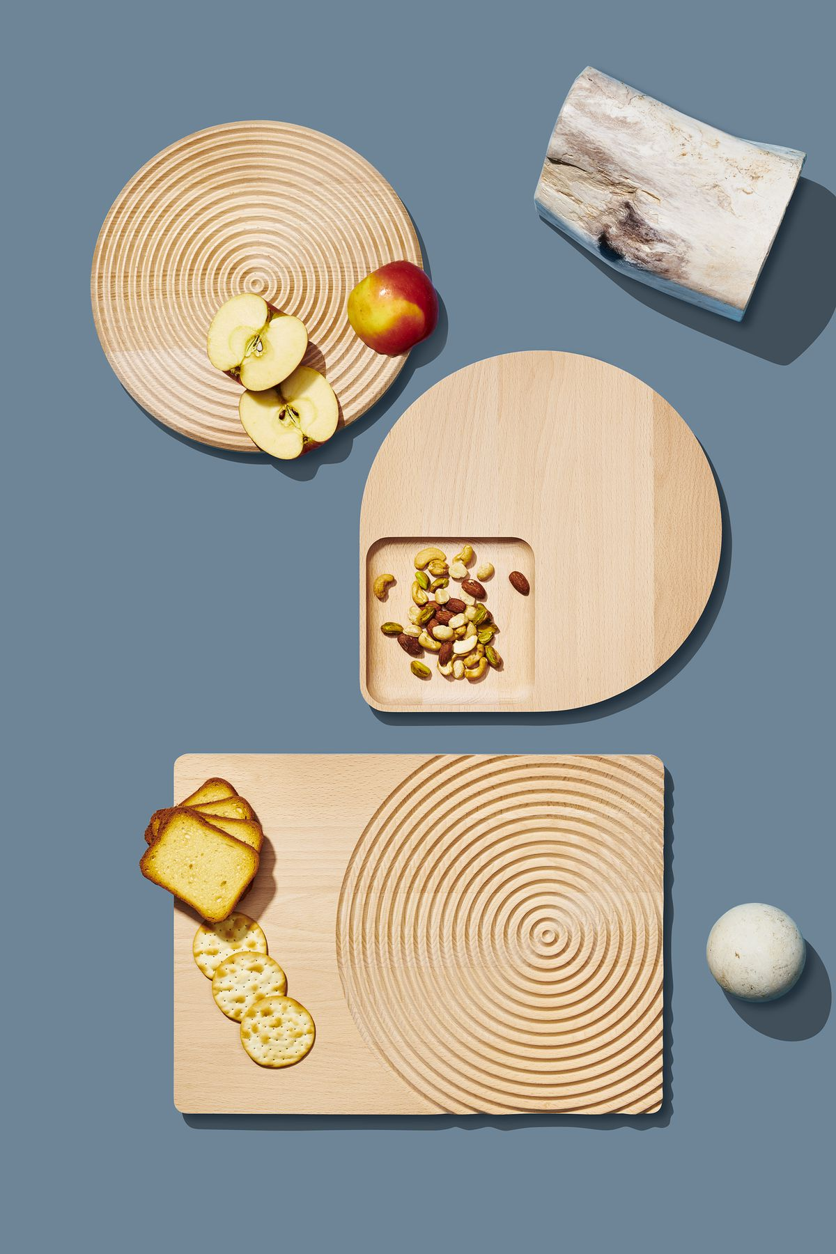 A group of three wooden cutting boards which are part of the Curbed Holiday Gift Guide 2019. On the cutting boards are crackers, bread, a sliced apple, and assorted nuts. There are various design objects arranged around the boards.