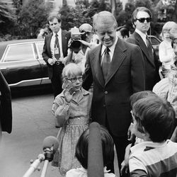 FILE - In this June 8, 1977 file photo, President Jimmy Carter stands with his daughter Amy as she waves to other children on the street in the Georgetown section of Washington, guarded by Secret Service agents. Carter went to Georgetown to dine at the home of Management and Budget Director Bert Lance. The Secret Service has been tarnished by a prostitution scandal that erupted April 13, 2012 in Colombia involving 12 Secret Service agents, officers and supervisors and 12 more enlisted military personnel ahead of President Barack Obama's visit there for the Summit of the Americas.