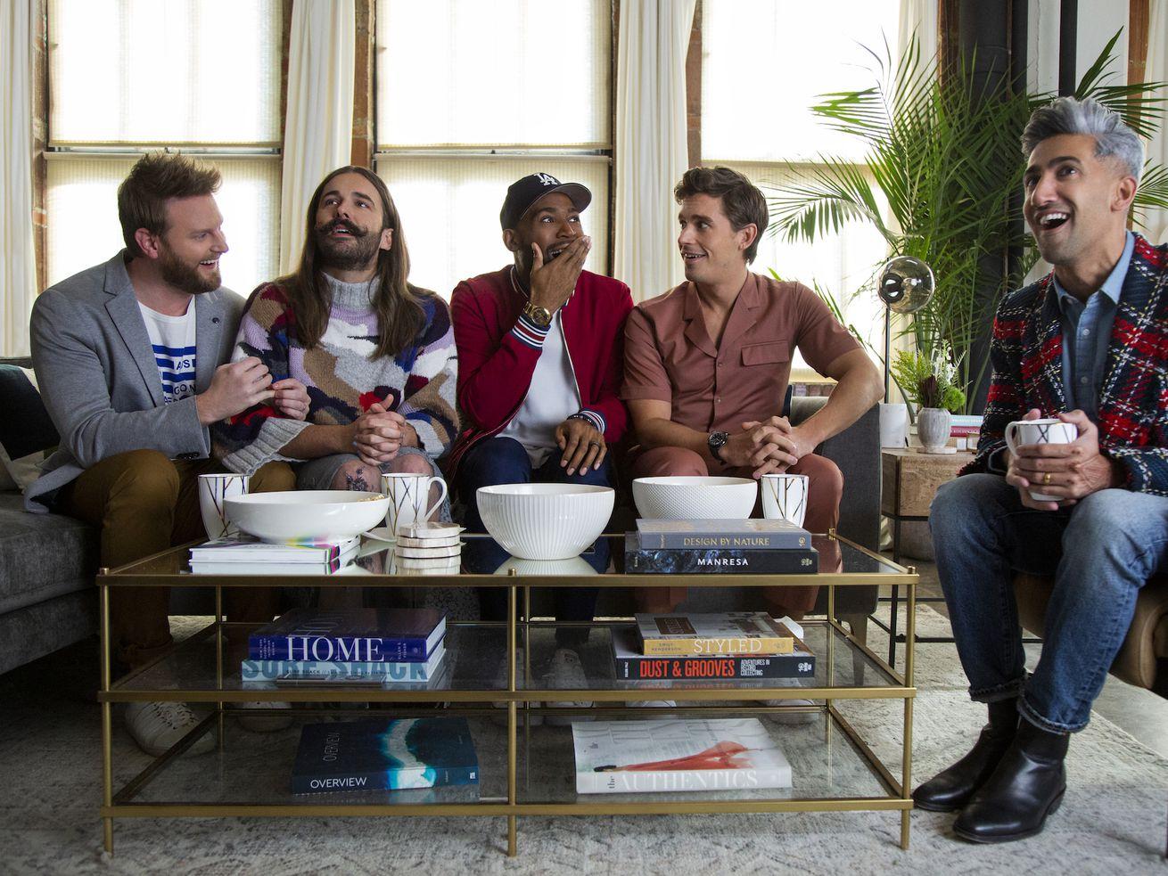 Bobby Berk, Jonathan Van Ness, Karamo Brown, Antoni Porowski, and Tan France sit on a modern sofa laughing