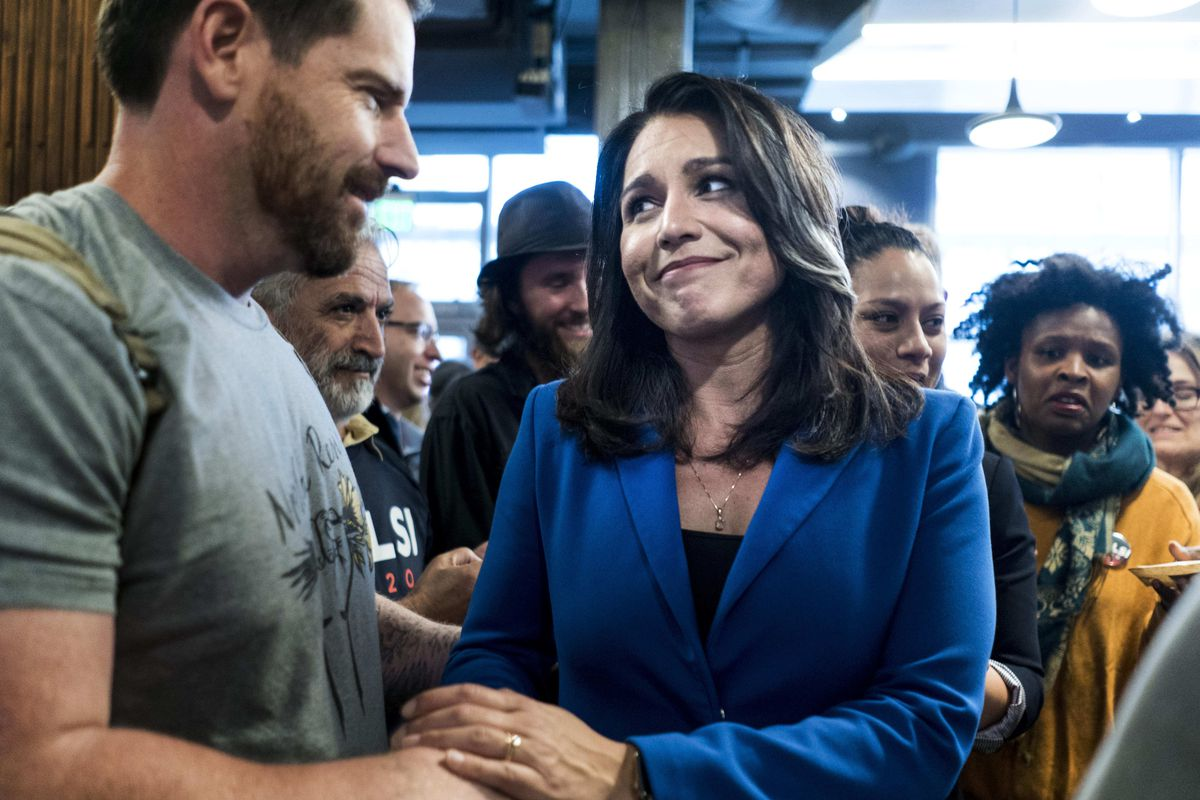 Tulsi Gabbard shakes hands with a supporter.