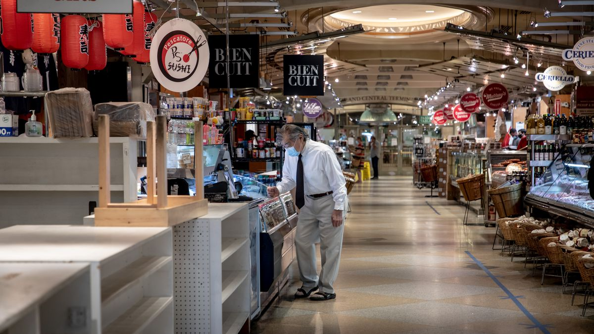 A man in a face mask looks at food stalls in Grand Central Market
