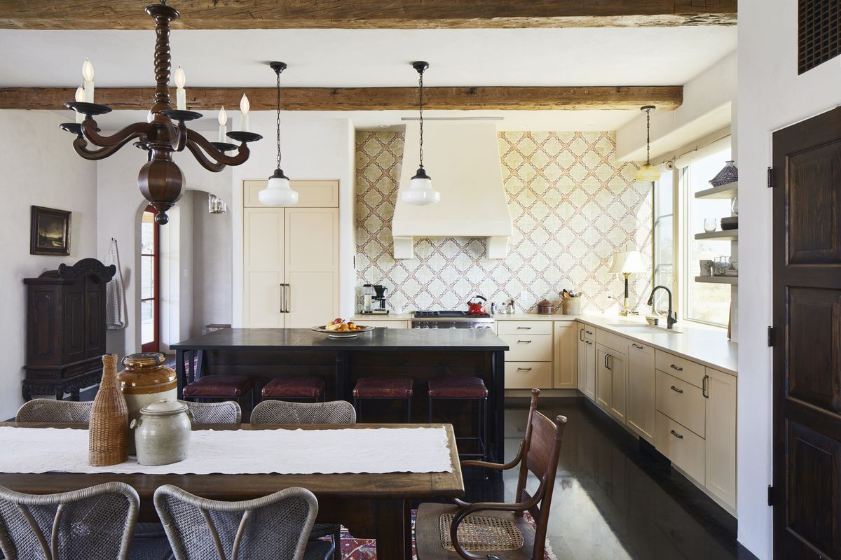 Counter-to-ceiling tile is done in a classic, garden trellis pattern. The kitchen cabinetry and range hood are cream colored. An antique table, chairs, and light fixture are in the foreground.