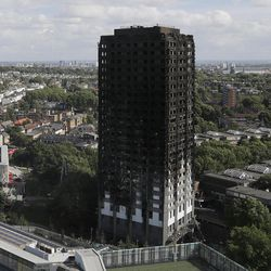 The scorched facade of the Grenfell Tower in London, Thursday, June 15, 2017, after a massive fire raced through the 24-storey high-rise apartment building in west London early Wednesday.  Firefighters are beginning the task of combing through the devastated apartment tower, Thursday, checking integrity of the structure and searching to find victims.
