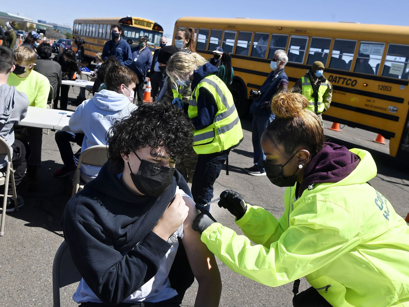 In this April 26, 2021, file photo, CREC Academy of Aerospace and Engineering sophomore Brian Acevedo, 16, receives a COVID-19 vaccine from nurse Myra Glass, of East Hartford, during a mass vaccination site at Pratt & Whitney Runway in East Hartford, Conn.