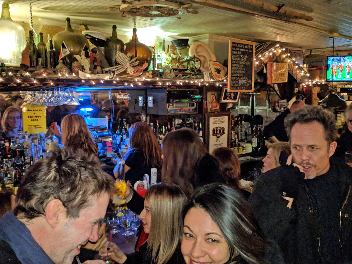 Groups of people talk closely in a dive bar with empty liquor bottles and colorful lights