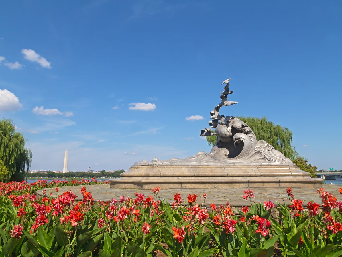 A statue of seagulls and a wave, surrounded by red tulips. The Washington Monument, a tall obelisk, is in the background.