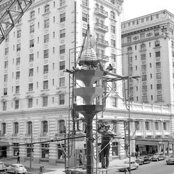 Workmen put a beehive topped by an eagle atop a standard across from the Brigham Young statue and Hotel Utah honoring the pioneers as part of a year long recognition.