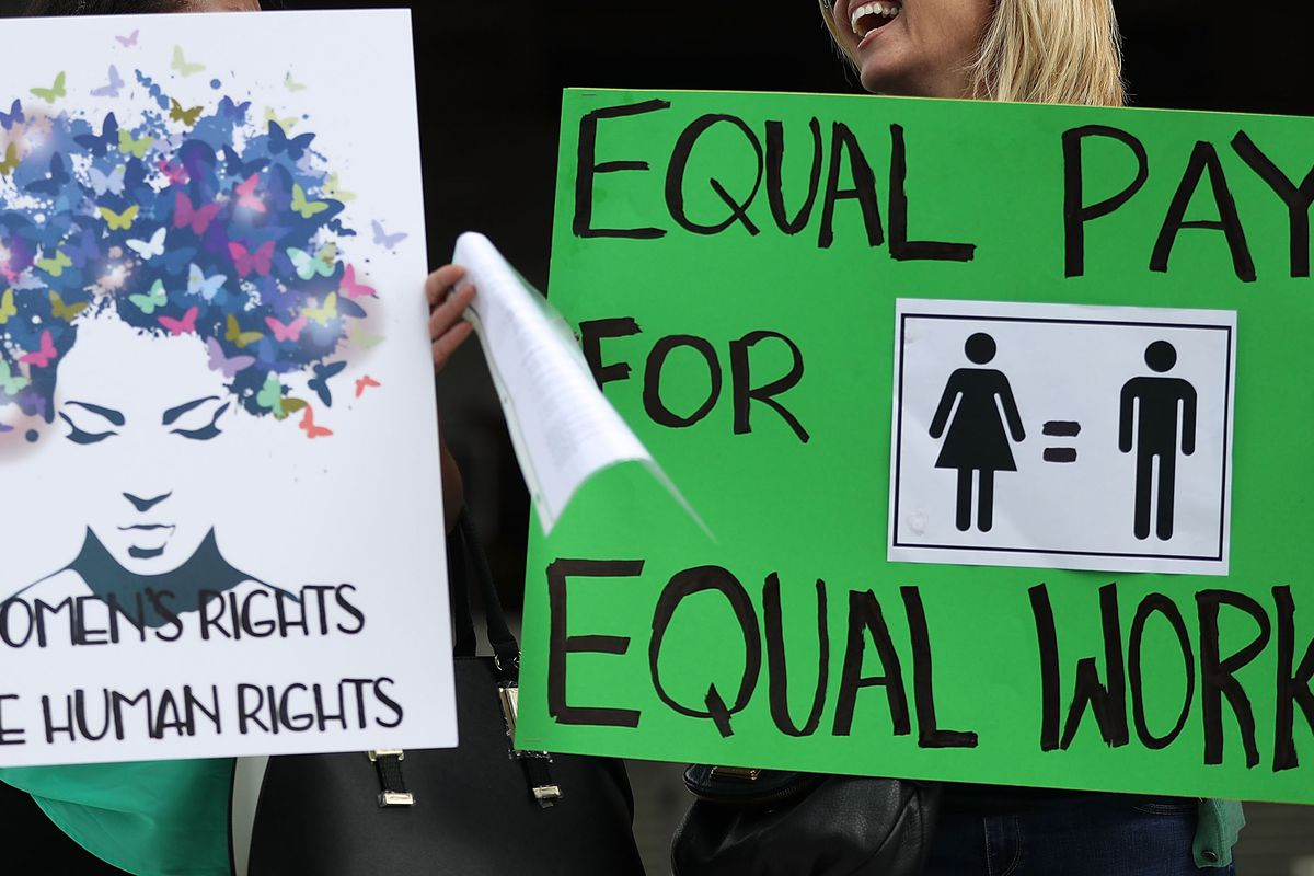 Women hold signs at a rally for equal pay last month in Fort Lauderdale, Fla.
