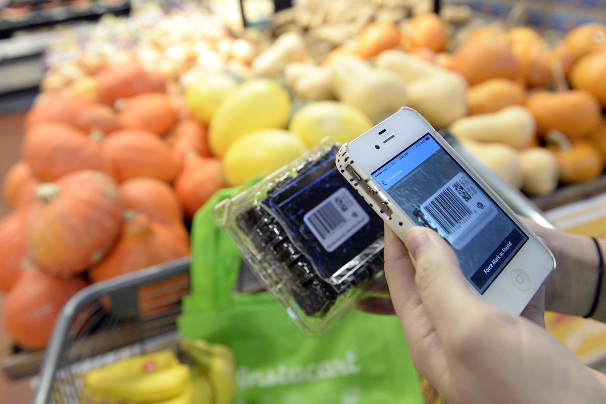 A hand holding a phone with the Instacart app on it, in front of a box of fruit