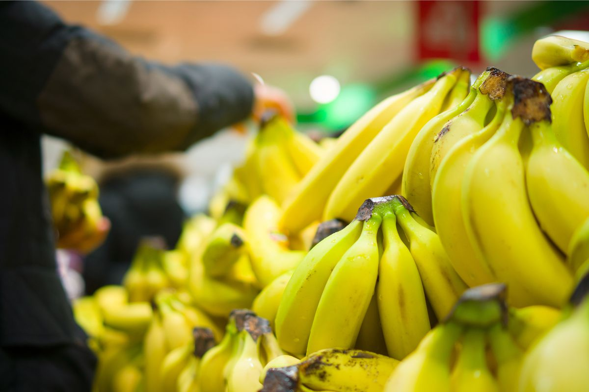 A closeup shot of bananas at a grocery store, with a shopper selecting some in the background.