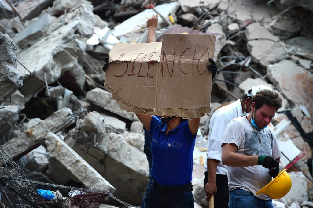 Rescuers searching for survivors buried under the rubble and debris of a building flattened by a 7.1-magnitude quake ask for silence in Mexico City on September 19, 2017. | Ronaldo Schemidt/AFP/Getty Images
