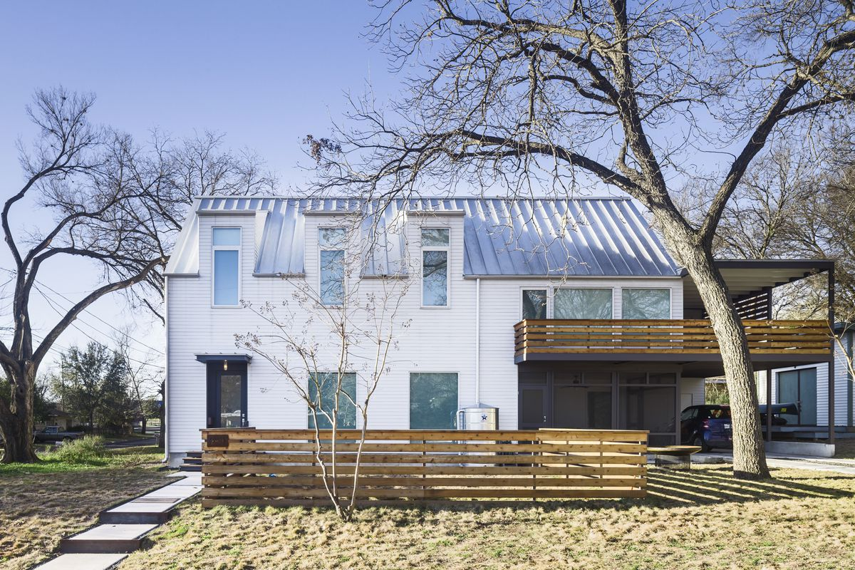A modern house with a metal roof that references Dutch and farmhouse architecture.
